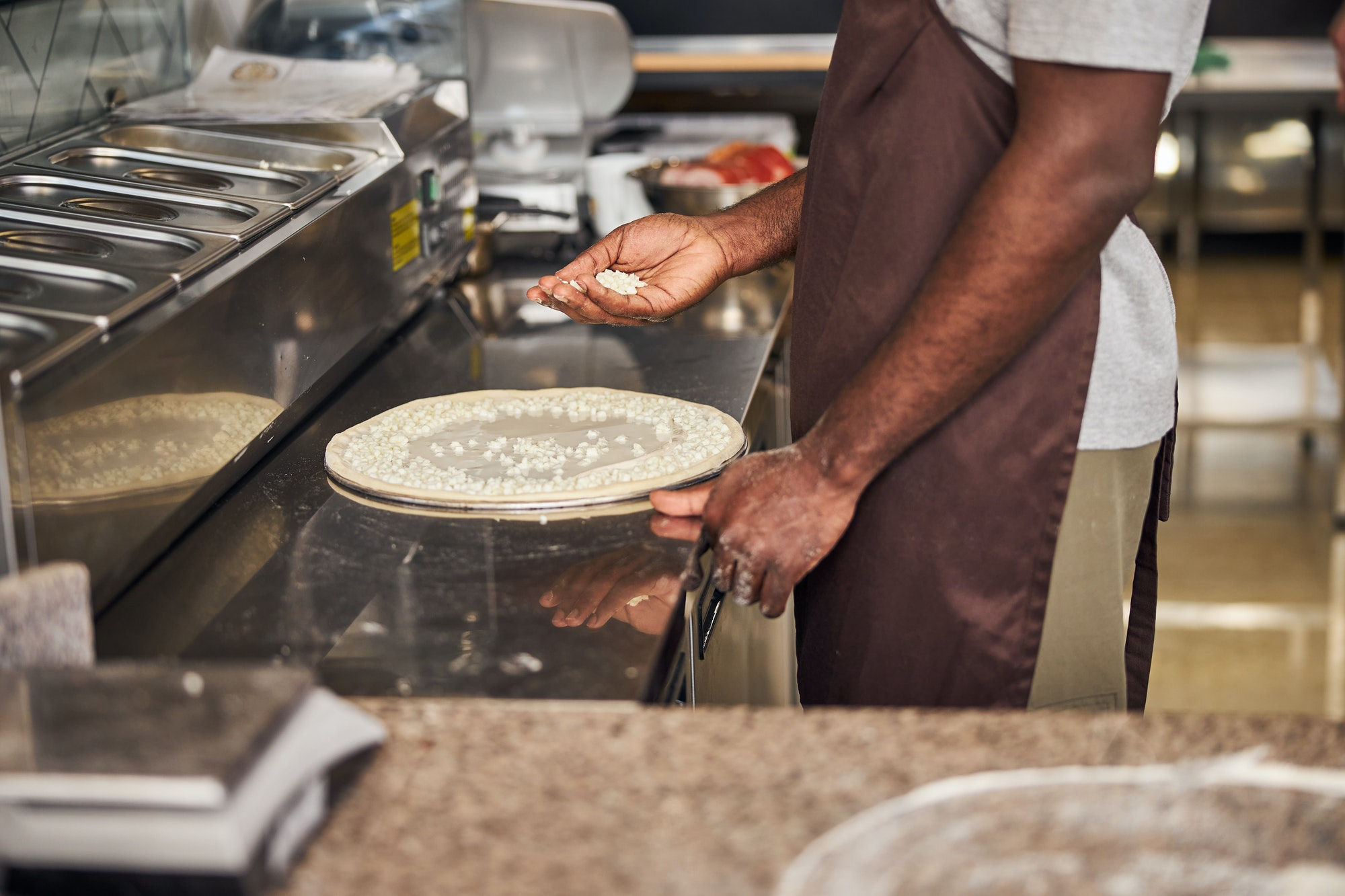 Afro American man cooking pizza in restaurant